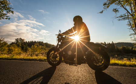 city of sunrise: Man seat on the motorcycle on the forest road during sunrise.