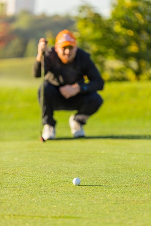 Close-up of golf ball with player. Stock Photo
