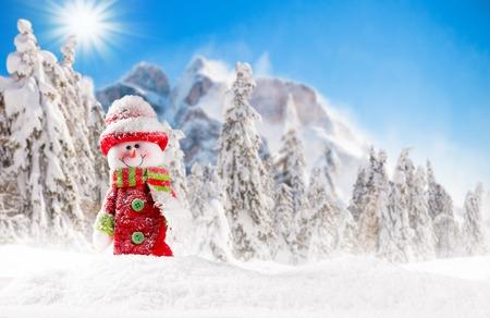 montañas nevadas: Fondo de Navidad con muñeco de nieve y la alta montaña.