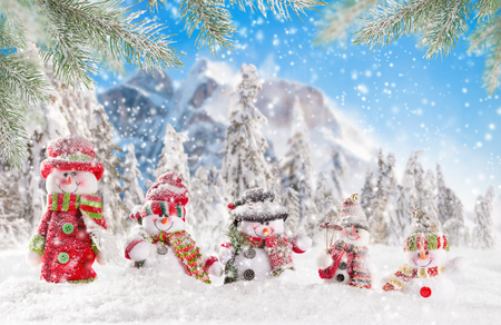 winter holiday: Christmas background with snowmen and high mountains.