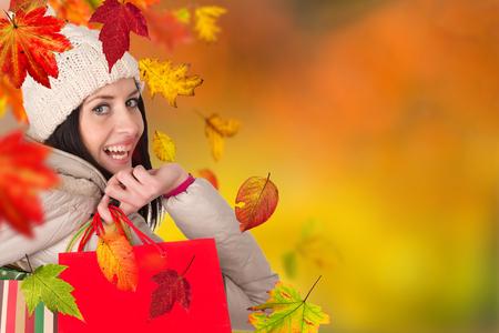 shopper: Beautiful woman holding shopping bags, buying in autumn season. Happy female shopper.