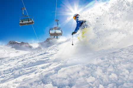 lift: Skier skiing downhill during sunny day in high mountains