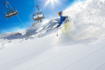 to ski: Skier skiing downhill during sunny day in high mountains