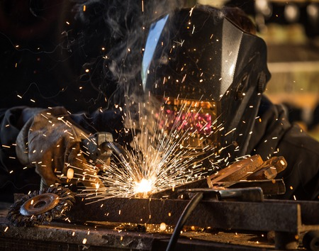 welding mask: Working welder in action with bright sparks. Stock Photo