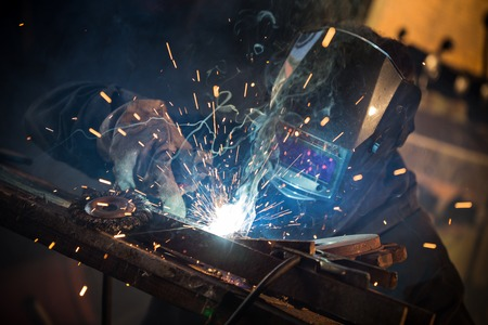 manual worker: Working welder in action with bright sparks. Stock Photo