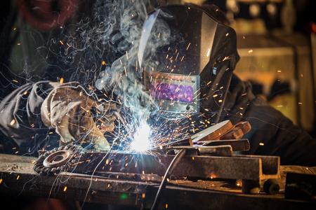 Working welder in action with bright sparks. Standard-Bild