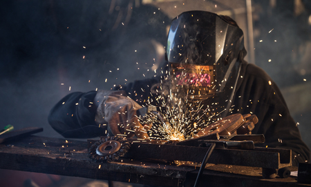 manufacture: Working welder in action with bright sparks. Stock Photo