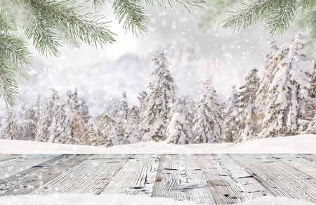 Abstract Christmas background with falling snow flakes and wooden table