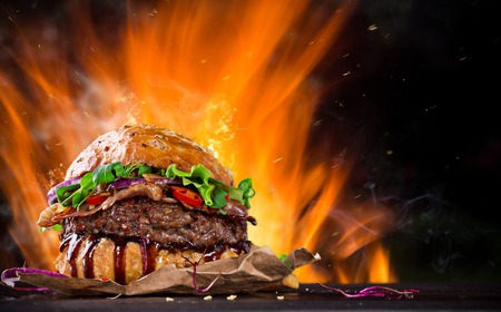 HAMBURGUESA: El hogar hizo la hamburguesa con llamas de fuego, primer plano.
