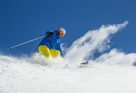 downhill skiing: Skier skiing downhill during sunny day in high mountains