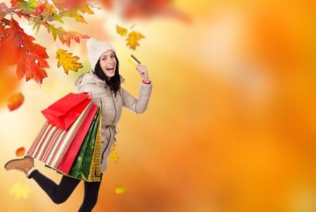 outstretching: Beautiful woman holding shopping bags, buying in autumn season. Happy female shopper.