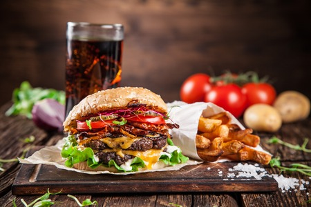 american cuisine: Close-up of home made burgers on wooden background