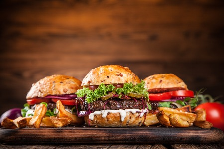 food menu: Close-up of home made burgers on wooden background