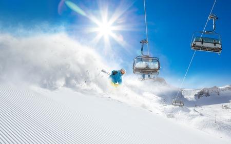 SKI: Skier skiing downhill in high mountains