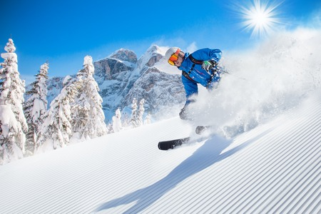 to ski: Skier skiing downhill in high mountains