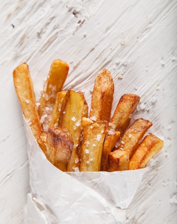 Close-up home made French Fries on White wooden table