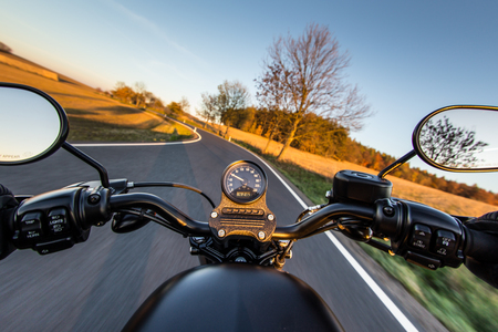 handlebars: The view over the handlebars of a speeding motorcycle