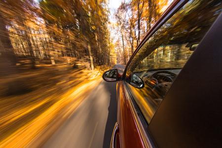 speeding car with motion blur background during autumn day