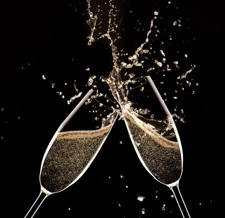 felicitaciones: Vidrios de champán con splash, aislado en negro