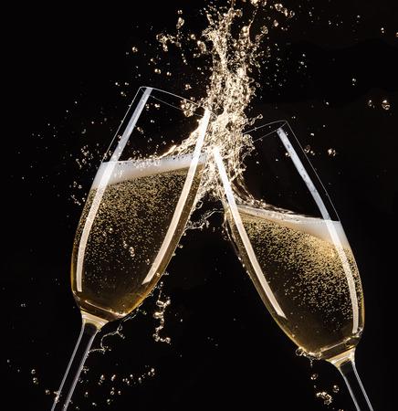 Glasses of champagne with splash, isolated on black Standard-Bild