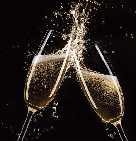 wine glasses: Glasses of champagne with splash, isolated on black Stock Photo