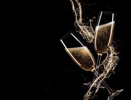 brindisi spumante: Bicchieri di champagne con spruzzi, isolato su fondo nero