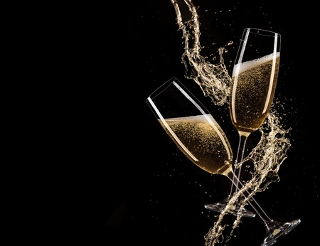 Glasses of champagne with splash, isolated on black Foto de archivo