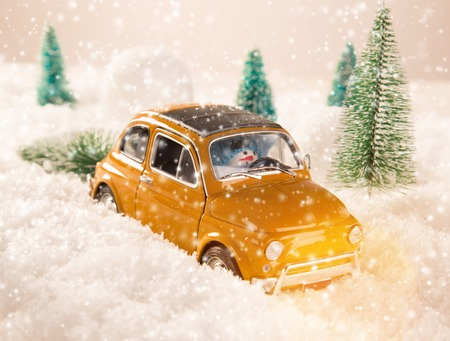 miniature: Miniature yellow car with spruce trees. Christmas theme.