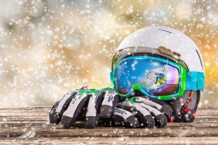 ski mask: Colorful ski glasses, gloves and helmet on wooden table. Winter ski theme.