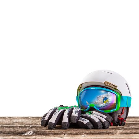 guantes: Coloridas gafas de esquí, guantes y casco en la mesa de madera. Tema de esquí de invierno. Foto de archivo