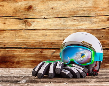 equipment: Colorful ski glasses, gloves and helmet on wooden table. Winter ski theme.