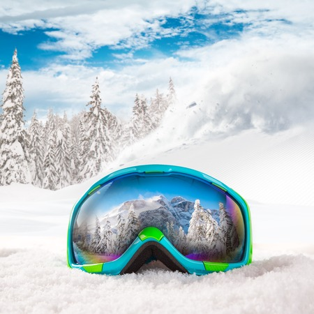 snowboard: Colorful ski glasses on snow. Winter ski theme.
