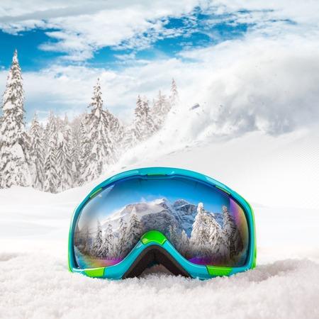 extreme weather: Colorful ski glasses on snow. Winter ski theme.