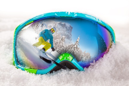 Colorful ski glasses on snow. Winter ski theme.