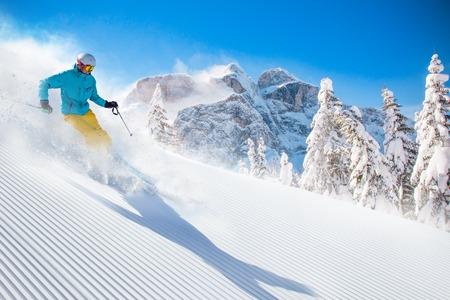 高山の日当たりの良い日中に下り坂をスキー スキーヤー