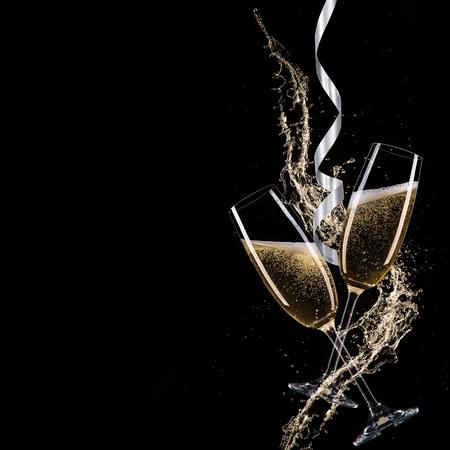 Glazen champagne met plons, geïsoleerd op zwart