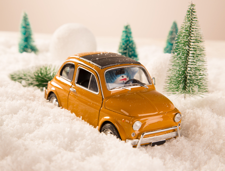 christmas trees: Miniature yellow car with spruce trees. Christmas theme.