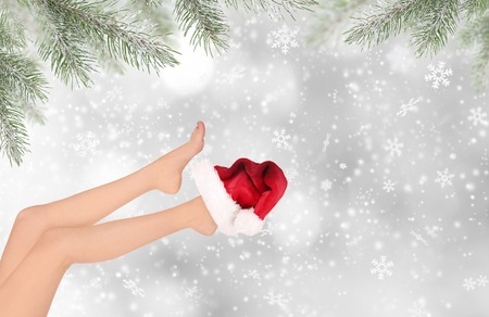 hat nude: woman legs with santa cap, beauty treatment of christmas Stock Photo