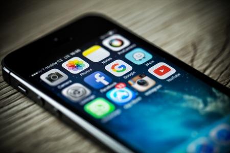 PRAGUE, RÉPUBLIQUE TCHÈQUE - 17 novembre 2015: Une photo close-up d'Apple iPhone 5s écran de démarrage avec applications icônes. icônes de médias sociaux populaires sur l'écran du téléphone intelligent.