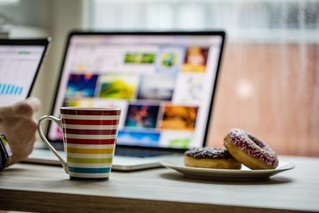 El hombre trabaja en el cuaderno, con una taza de té o café. Concepto de trabajo a domicilio.