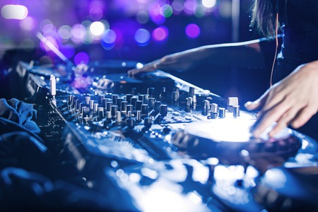dj: Dj mixes the track in the nightclub at party, close-up. Stock Photo
