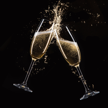 Glasses of champagne with splash, isolated on black 免版税图像