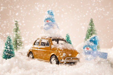 snow tree: Miniature yellow car with spruce trees. Christmas theme.