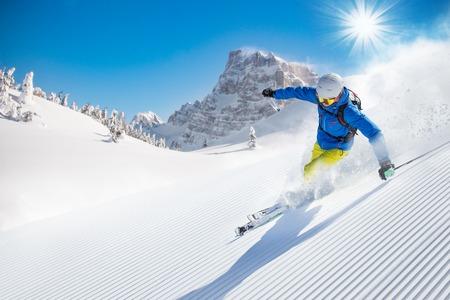 in action: Esquiador del esquí alpino durante el día soleado en alta montaña Foto de archivo