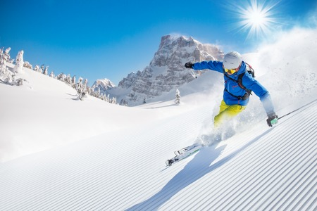 Skier skiing downhill during sunny day in high mountains Stok Fotoğraf - 48434650