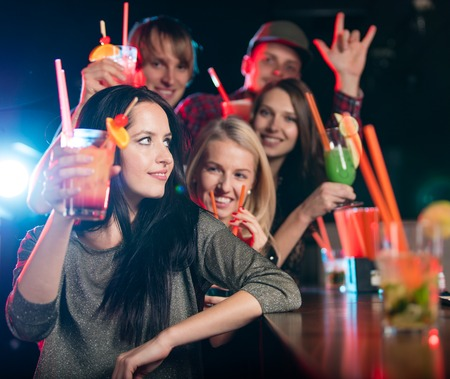 girl drinking: Group of young people having fun in club, celebration theme.