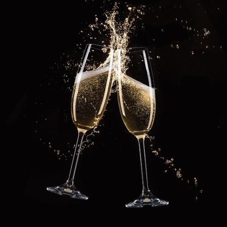 Glazen champagne met plons, geïsoleerd op zwart Stockfoto