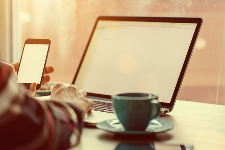 laptop home: Man working on notebook, with a fresh cup of tea or coffee. Home work concept.