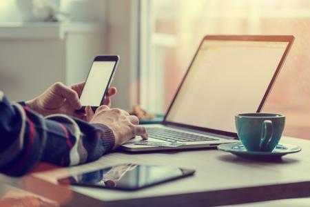 남자는 차 또는 커피의 신선한 컵, 노트북에서 작동합니다. 홈 작업 개념.