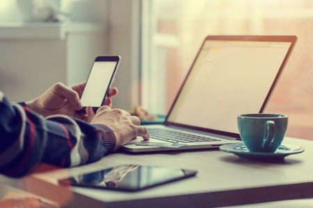 Man working on notebook, with a fresh cup of tea or coffee. Home work concept.